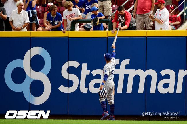 [사진] LA 다저스의 무키 베츠가 20일(한국시간) 신시내티와의 원정 경기에서 상대 선수의 메이저리그 1호 홈런 볼을 찾아준 뒤 자신의 사인 배트를 홈런 볼을 돌려준 관중에게 선물하고 있다. ⓒGettyimages(무단전재 및 재배포 금지)